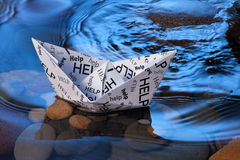Paper Boat Help Stress Anxiety. A conceptual image of a white paper boat with help written all over, floating on water rocks and waves stock photos
