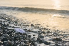 Paper boat lies on the seafront at sunrise. Lonely white paper boat lies on the beach with stones at sunrise royalty free stock photos