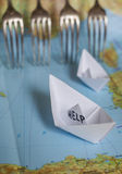 Paper Boat Map Fence Refugees. White paper boat onto world map with Help sign on it royalty free stock photo