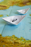 Paper Boat Map Help Refugees. White paper boat onto world map with Help sign on it royalty free stock photos