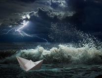 Paper boat in ocean storm with lgihting and waves Royalty Free Stock Images