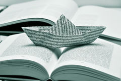 Paper boat on an open book, black and white Stock Photos