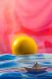 Paper boat and an orange as the sun Stock Images