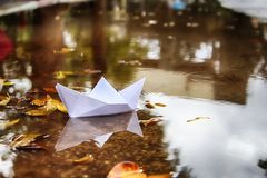 Paper Boat Origami Ship sails in a puddle formed after rain. Winter in Israel. Paper Boat Origami Ship sails in a puddle formed after rain. Winter in Israel stock photography