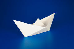 Paper boat. Over blue background Stock Image