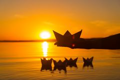Paper boat is on a palm of boy on the background of four paper origami which float in the river at sunset royalty free stock photography