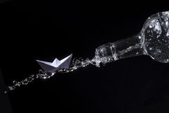 Paper boat rides on a water splash out of a bottle against black Royalty Free Stock Images