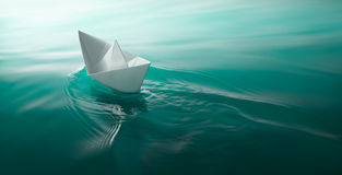Paper boat sailing. Origami paper boat sailing on water causing waves and ripples