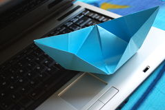 Paper boat sailing on laptop Royalty Free Stock Images
