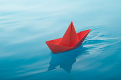 Paper boat sailing. Red paper boat sailing on water causing waves and ripples royalty free stock image