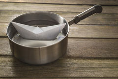 Paper boat sailing in a saucepan Royalty Free Stock Photo