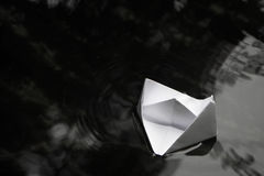 Paper boat sailing on water surface Stock Photos