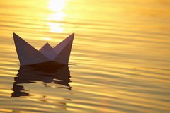 Paper boat sailing on water with waves. And ripples Royalty Free Stock Photos