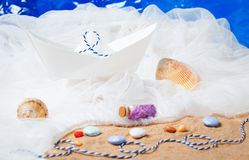 Paper boat with sand, ropes, water Royalty Free Stock Photography
