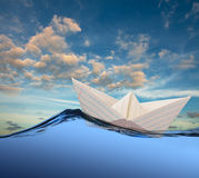 Paper boat in the sea. White paper boat floating in the sea stock photography