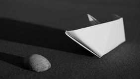Paper boat and sea shell Royalty Free Stock Image