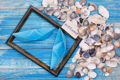 Paper Boat with shells and photo frame Stock Photo