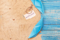 Paper Boat with shells and sand with sign - Welcome. Vocation and travel background Stock Photography