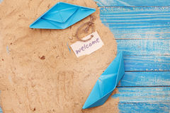Paper Boat with shells and sand with sign - Welcome. Vocation and travel background Royalty Free Stock Photos