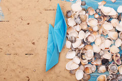 Paper Boat with shells and sand. Vocation and travel background Stock Image