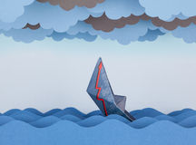 Paper boat is sinking into paper sea. Stock Images