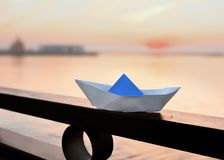A paper boat stands on an iron black fence on the background of the river. stock photo