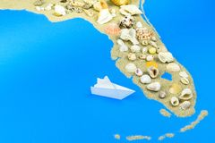 Paper boat stands off the coast of Florida. A paper boat stands off the coast of Florida. The contours of Florida are lined with sand, on top are seashells royalty free stock photos