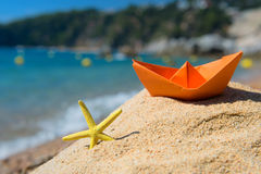 Paper boat and starfish at the beach. Paper boat and starfish in the sand at the beach Stock Photo