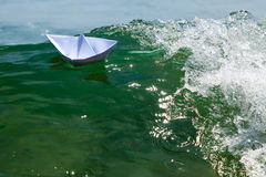 Paper boat struggling with a huge Stock Images