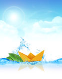 Paper Boat in Water. Paper boat and leaves floating in cool splashy water Stock Photo