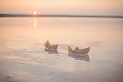 Paper boat. On water at sunset stock photo