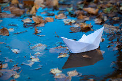 Paper boat on water. Toy paper boat on a blue water with dirty tree leaves stock photography