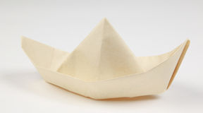 Paper boat on white. A hand-made paper boat against white background Royalty Free Stock Image