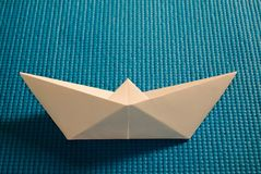Paper boat. White paper boat on the rubber blue surface Stock Images