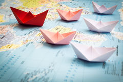 Paper boats following a red leader boat. On world map. Concept for leadership, teamwork and winning success stock photography