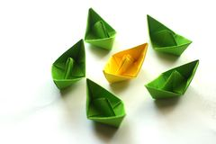 Group of origami paper ships in green and yellow colors. stock photos