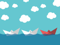 Paper boats, leadership concept. Red paper boat leading white ones sailing in sea on blue sky background. Leadership, success, teamwork and management concept Royalty Free Stock Photography