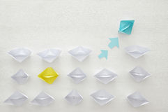 paper boats and one individual boat choosing different path Stock Images