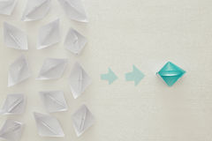 Paper boats and one individual boat choosing different path. Top view image of paper boats over wooden background and one individual boat choosing different path Royalty Free Stock Images