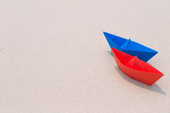 Paper boats on seashore. Blue and red paper boats on seashore, white sand royalty free stock photography