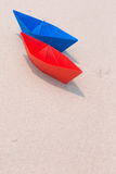 Paper boats on seashore. Red and blue paper boats on seashore, white sand stock image