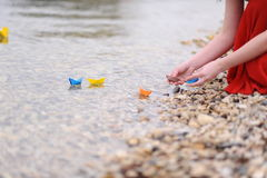 Paper boats with woman hands. Colorful paper boats on water with woman hands Royalty Free Stock Photography