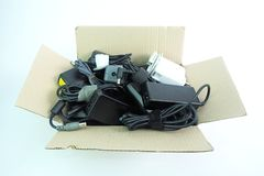 Paper box with the damaged or old used Adapter power charger of laptop computer or electrical appliances on white stock images