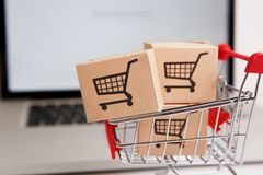 Many paper boxes in a small shopping cart on a laptop keyboard. Concepts about online shopping that consumers can buy royalty free stock image