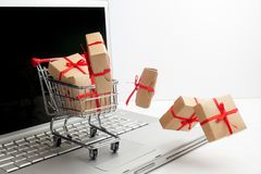 Paper boxes in a shopping cart on a laptop keyboard. Ideas about e-commerce, a transaction of buying or selling goods or Royalty Free Stock Photo