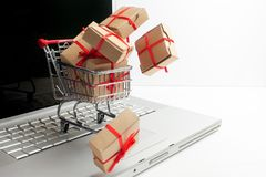 Paper boxes in a shopping cart on a laptop keyboard. Ideas about e-commerce, a transaction of buying or selling goods or Stock Photos