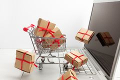 Paper boxes in a shopping cart on a laptop keyboard. Ideas about e-commerce, a transaction of buying or selling goods or Stock Image