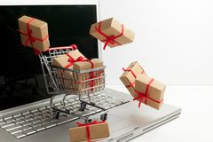 Paper boxes in a shopping cart on a laptop keyboard. Ideas about e-commerce, a transaction of buying or selling goods or. Paper boxes in a shopping cart on a royalty free stock images