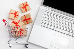Paper boxes in a shopping cart on a laptop keyboard. Ideas about e-commerce, a transaction of buying or selling goods or Royalty Free Stock Photography