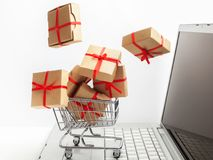 Paper boxes in a shopping cart on a laptop keyboard. Ideas about e-commerce, a transaction of buying or selling goods or Royalty Free Stock Image
